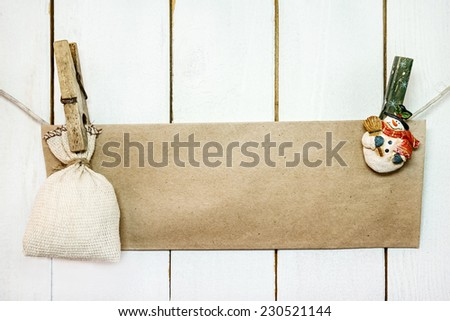 Christmas snowman clothespines hanging on clothesline or rope and holding brown craft paper card and sack on wood background - stock photo