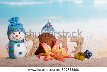 Christmas snowman, coconut and the inscription 2017 in the sand, decorated with a flower and gifts on the background of the sea