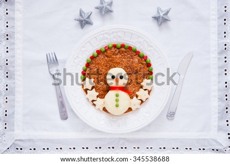 Christmas snowman dinner. Snowman made from mashed potatoes and decorated meat stews and vegetables. - stock photo