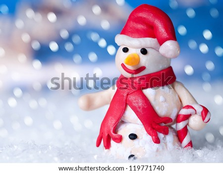 Christmas snowman in santa claus hat at winter - stock photo