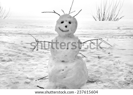 Christmas snowman sitting in a snowy outdoors - stock photo