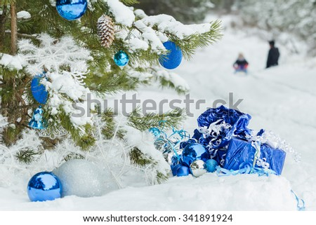 Christmas snowy pine tree decorated with shiny baubles and two children are sledging on snow covering  - stock photo
