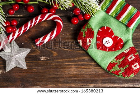christmas sock, candy cane and branches decoration on wooden table