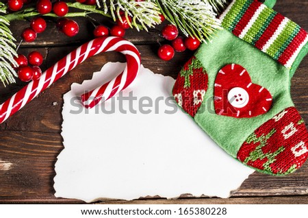 christmas sock, candy cane and branches decoration on wooden table, copy space - stock photo