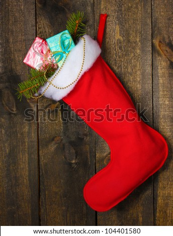Christmas sock with gifts on wooden background - stock photo