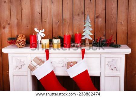 Christmas socks hanging on fireplace in room - stock photo
