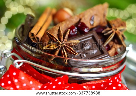 Christmas spices in a jar on festive background.