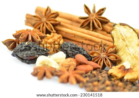 Christmas spices, nuts and dried fruits on white background - stock photo