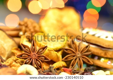 christmas spices, nuts, cookies and dried fruits on bokeh background - stock photo