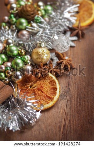 Christmas spices with orange and decoration on wooden board