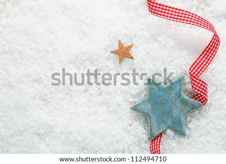 Christmas star background with a decorative red and white checked ribbon on a backdrop of winter snow with copysapce for your seasonal greetings - stock photo