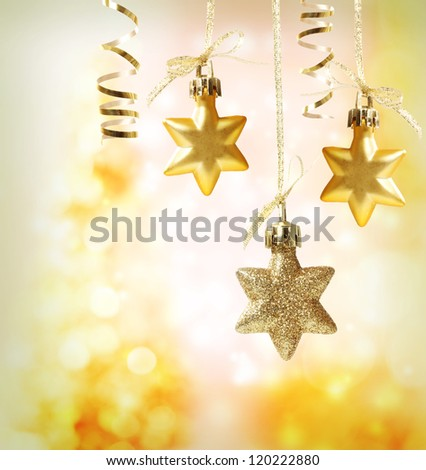 Christmas star ornaments over yellow orange lights background