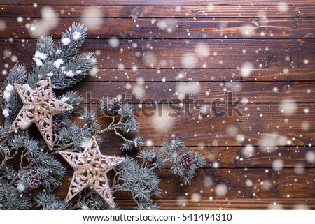 Christmas stars and branches fur tree on  wooden background. Decorative christmas composition. Selective focus. Place for text. Drawn snow.