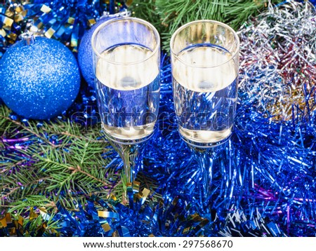 Christmas still life - above view of two glasses of champagne with blue Xmas decorations on Christmas tree background - stock photo