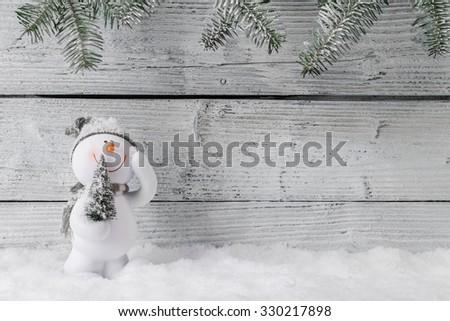 Christmas still life decoration with snowman on wooden background. - stock photo