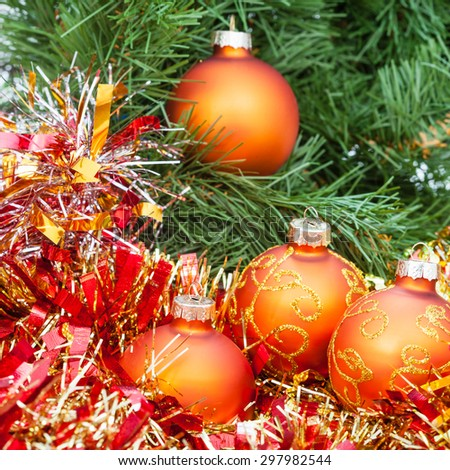 Christmas still life - four orange and yellow Christmas balls, red tinsel on green Xmas tree background - stock photo