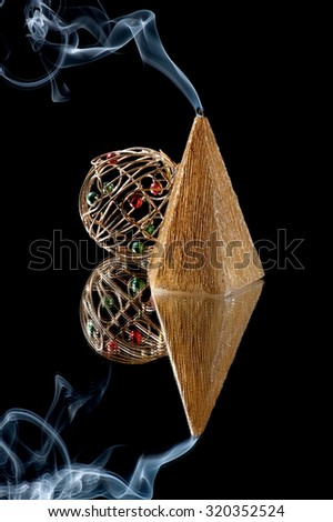 Christmas still-life from candles in the shape of a pyramid and the Christmas decorations standing in the mirror - stock photo