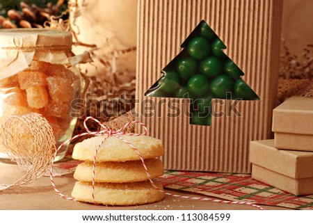 Christmas still life of food gifts with eco friendly wrapping paper and gift packaging (pine cones in background)  Close-up with shallow dof.  Selective focus on cookies tied with baker's twine.