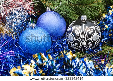 Christmas still life - one black glass and two blue and violet Christmas balls, tinsel on Xmas tree background - stock photo
