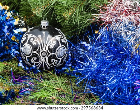 Christmas still life - one black glass Christmas ball, blue tinsel on Xmas tree background - stock photo
