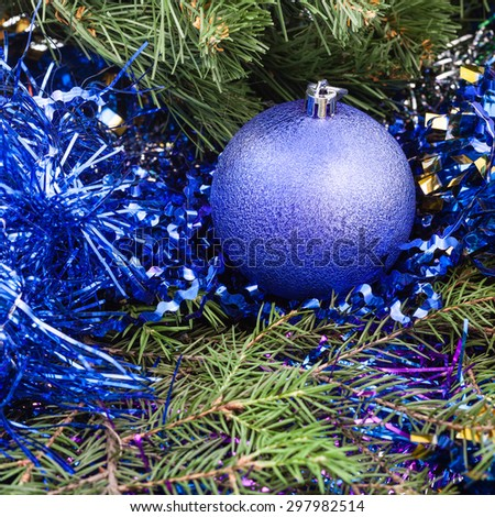 Christmas still life - one violet Christmas bauble, tinsel on Xmas tree background - stock photo