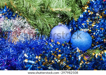 Christmas still life - pair of blue and violet Christmas balls, tinsel on Xmas tree background - stock photo