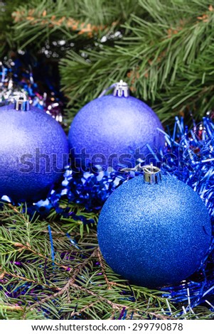 Christmas still life - three blue and violet Christmas balls close up, tinsel on Xmas tree background - stock photo