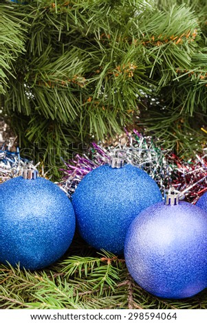 Christmas still life - three blue and violet Christmas balls, tinsel on Xmas tree background - stock photo