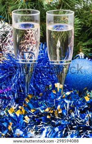 Christmas still life - Two glasses of champagne with blue Xmas decorations on green Christmas tree background - stock photo