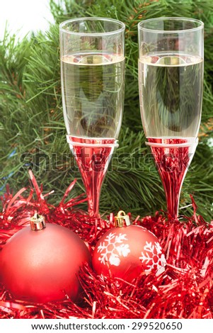 Christmas still life - Two glasses of champagne with red Xmas balls and tinsel on Christmas tree background - stock photo