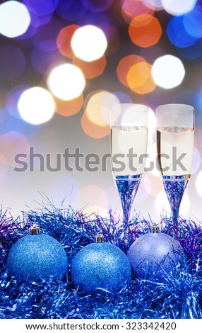 Christmas still life - two glasses of sparkling wine at blue Xmas decorations with pink and violet blurred Christmas lights bokeh background - stock photo