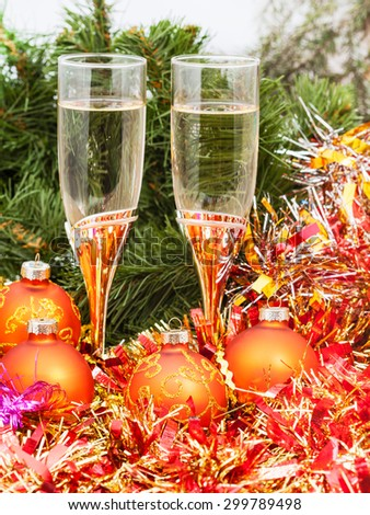 Christmas still life - Two glasses of sparkling wine with golden Xmas decorations on Christmas tree background - stock photo