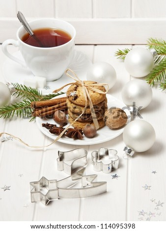 christmas still life with biscuits and a cut of tea on white wooden background - stock photo