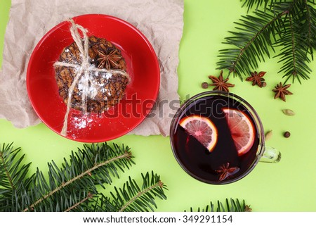 Christmas still life with branches of pine needles on a green paper with star anise, spices, mulled wine with lemon and sweet homemade cookies on the red saucer.  - stock photo