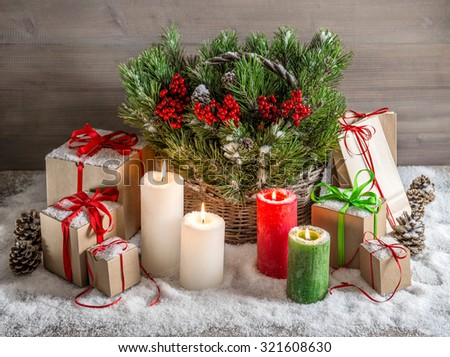 Christmas still life with burning candles and gift box. Festive decoration. Christmas tree branches in basket - stock photo