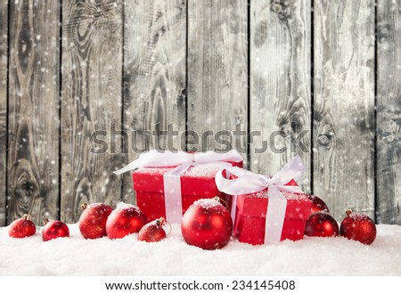Christmas still life with gifts in snow. Wooden planks as background - stock photo