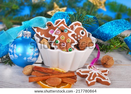 christmas still life with gingerbread cookies decorated with icing on wooden table - stock photo