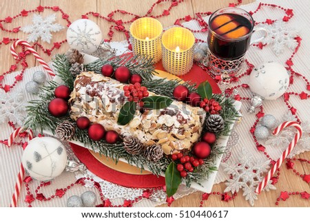 Christmas still life with stollen cake, mulled wine, candles, holly, fir, silver, red and white bauble decorations and glitter snowflakes on an oak table.