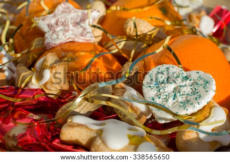 Christmas Still with Oranges Peanuts and Heart Decoration Covered with Angel Hair Closeup - stock photo