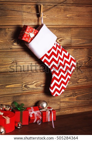 Christmas stocking and presents against wooden wall
