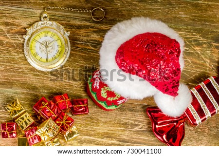 Christmas stocking, covered with Santa's cap, is on a scratched wooden table. Nearby lie decorative candy,pile of gifts and Christmas clock. Top view. Close-up.