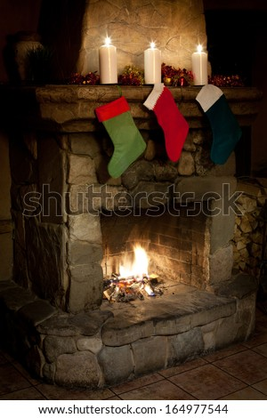 Christmas stocking on fireplace background. candles and woodpile. Chimney place. (left view). - stock photo