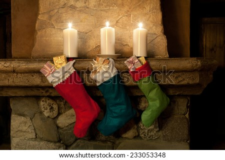 Christmas stocking on fireplace background. Chimney, candles. Christmas socks, decoration, gifts.  - stock photo