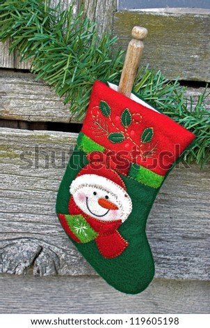 christmas stocking pinned to garland by old-fashioned clothespin - stock photo