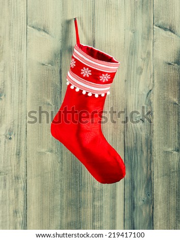 christmas stocking. red sock with white snowflakes hanging over rustic wooden background - stock photo