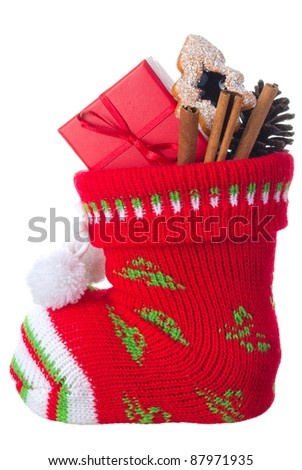 Christmas stocking stuffed with present box, cinnamon sticks and a cookie, isolated on a white background - stock photo