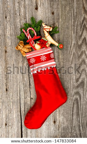 christmas stocking with nostalgic vintage toy decoration and pine branch over wooden background - stock photo