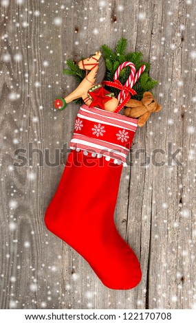 christmas stocking with nostalgic vintage toy decoration and snowflakes over wooden background - stock photo