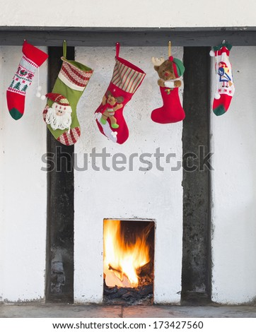 christmas stockings hanging on fireplace  - stock photo