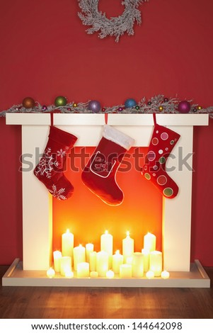 Christmas stockings hanging over fireplace - stock photo